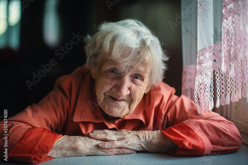 Leinwanddruck Bild Old woman sitting near window, close-up portrait.