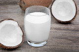 Coconut milk in a glass on old wood table - 207674489