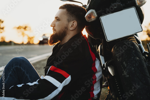 Side view of a young bearded man sitting on the ground leaning on his bike seriously and looking away resting near the road while adventuring on his motorcycle.