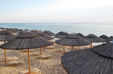 Straw umbrellas and chaise lounges on the beach in Greece. - 207676260