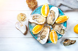 Fresh oysters close-up on blue plate, served table with oysters, lemon and champagne in restaurant. Gourmet food. Tabletop view - 207679419