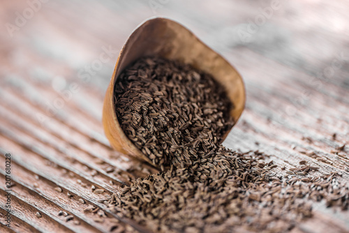 Fotobehang Koffiebonen loose cumin seeds in a small wooden dish o a table