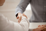 Close up of colleagues greeting with handshake, workers get acquainted at company briefing, worker shaking hand of associate congratulating, business partners closing deal. Cooperation, HR concept