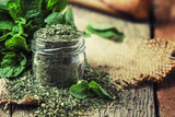Dried peppermint in a glass jar and a bunch of fresh mint, vintage wood background, selective focus - 207695285