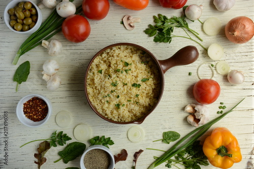 Bulgur in plate on wooden table. Traditional middle eastern or arab dish. Top view. vegetarian dinner. Bulgur  with vegetables, spices on white background. Flat la - 207696088