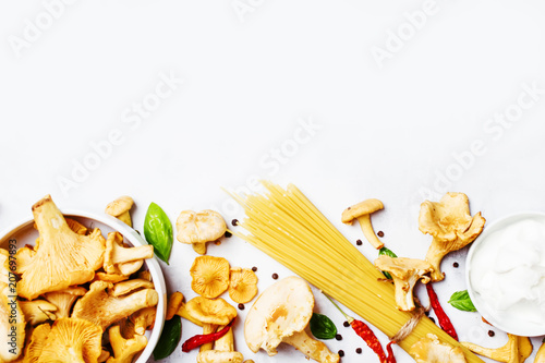 Leinwanddruck Bild Ingredients for cooking pasta with mushrooms chanterelles in a creamy sauce, food background, top view