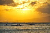 A group of surfers catching some waves off the coast of Oahu during sunset.