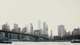 Beautiful background shot of sunset Brooklyn Bridge and New York cityscape skyline. Boat passing by on the river 4K. - 207701835