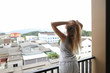 Young blonde girl with raised hands wearing shorts and shirt standing on balcony and looking at buildings in background. Concept of fresh morning and mainly cloudy weather.