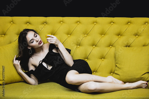 Model young woman beautiful and luxurious sitting with macaroon on bright yellow sofa happy and sexy