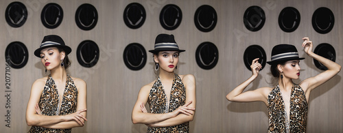 Model young brunette woman beautiful and luxurious in a fashionable dress with leopard print in retro style and hat