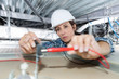 Leinwanddruck Bild - female electrician installing electric device in ceiling