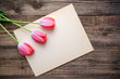 Three pink tulips and a sheet of paper on a wooden background