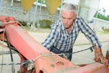 Farmer working on machinery - 207718638