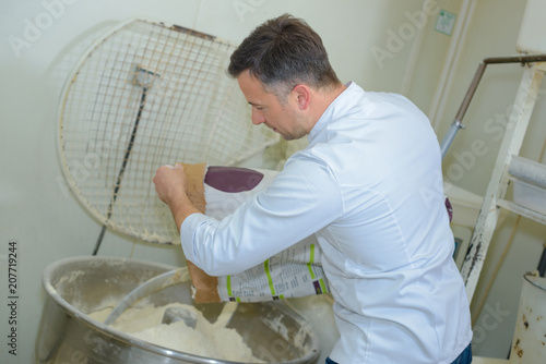 Man tipping flour into industrial vat