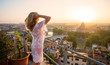 Woman feeling inspired at sunrise on terrace overlooking city