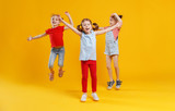 funny children girls jumping on colored yellow background - 207724056