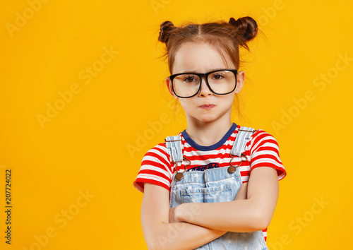 Leinwanddruck Bild funny child girl in glasses on colored background