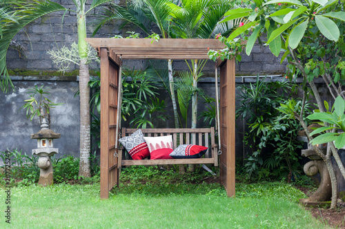Foto Murales Classic outdoor wooden swing in the green garden with pillows