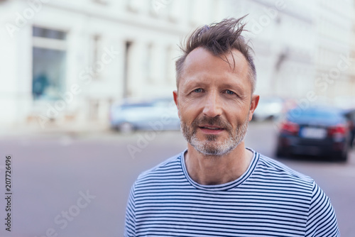 Thoughtful mature man standing in a windy street