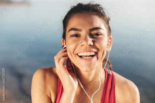 Fotobehang Muziek Close up of a happy sportswoman listening to music