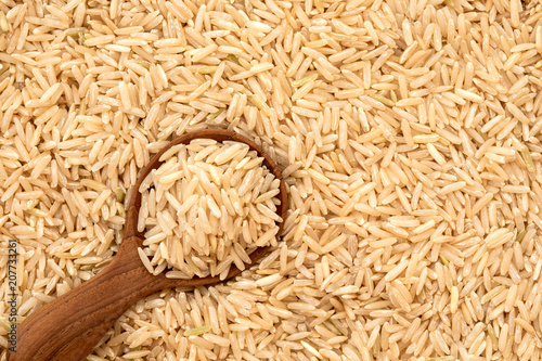Brown rice in wooden spoon on rice seed background