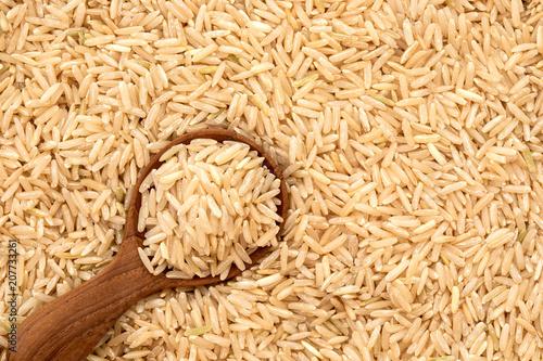 Brown ryż w drewnianej łyżce na ryżu ziarna tle