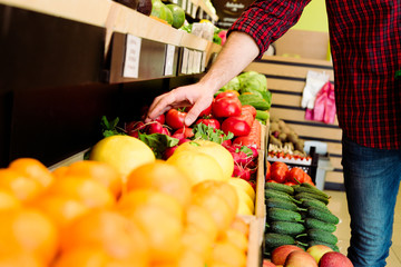 Man's hand selects fruits and vegetables from the supermarket shelves.