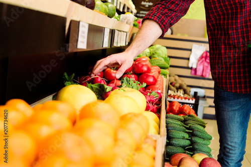 Foto Murales Man's hand selects fruits and vegetables from the supermarket shelves.