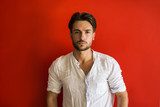 Stylish trendy young man standing outdoor against red wall, looking confindent at camera - 207737291