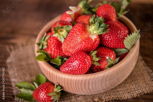 Foto Murales strawberries in wooden bowl on wood table