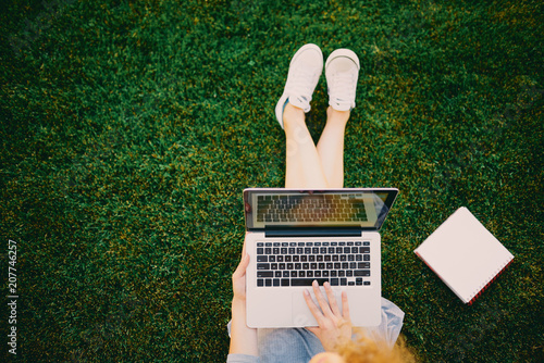 Foto Murales Aerial view of female student sitting on the grass and using laptop.