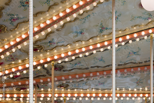 Fotobehang Amusementspark Closeup of lights of French carousel in a holiday park. traditional old fairground vintage carousel. Merry-go-round with horses.