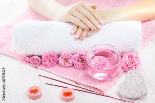 beautiful pink manicure with tea rose, candle and towel on the white wooden table.