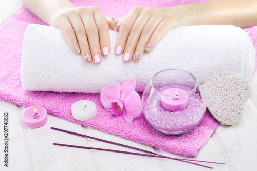 Fotobehang Manicure beautiful pink manicure with orchid, candle and towel on the white wooden table.