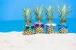 Leinwanddruck Bild - Tropical vacation travel concept, fresh pineapple on tropical white sand beach with sunglasses, Summer travel