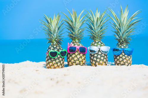 Leinwanddruck Bild Tropical vacation travel concept, fresh pineapple on tropical white sand beach with sunglasses, Summer travel