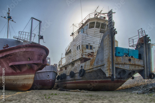 Fotobehang Schip Old rusty and rumpled river tug with some other boats and ships near by. HDR image