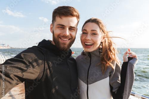 Joyful young sports couple taking a selfie