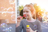 Cute girl playing with soap bubbles - 207758644