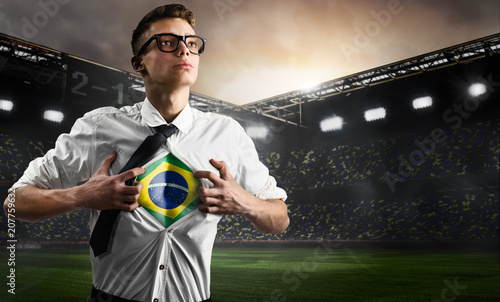 Foto Murales Brazil soccer or football supporter showing flag under his business shirt on stadium.