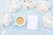 Leinwanddruck Bild - Morning coffee cup for breakfast, empty notebook and white peony flowers on blue pastel table top view. Woman working desk. Flat lay.