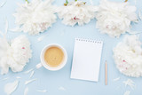 Morning coffee cup for breakfast, empty notebook and white peony flowers on blue pastel table top view. Woman working desk. Flat lay. - 207761847