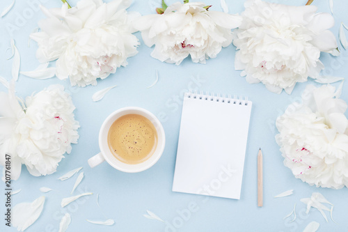 Leinwanddruck Bild Morning coffee cup for breakfast, empty notebook and white peony flowers on blue pastel table top view. Woman working desk. Flat lay.