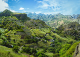 Cape Verde. Gorgeous panoramic view of famous fertile Paul Valley. Agriculture terraces of sugarcane in vertical valley sides, people dwellings, rugged peaks and motion clouds on horizon - 207764482