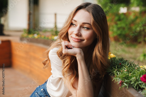 Smiling young girl in casual clothes looking away - 207765206