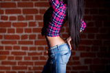 Sexy woman ass and back in jeans on red brick background. Girl with perfect torso bottom view.