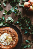 top view of homemade apple pie and fresh apples with green leaves on wooden tabletop - 207769857