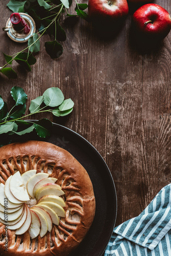 flat lay with arranged homemade apple pie, fresh apples with green leaves and linen on wooden tabletop