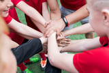 High angle closeup of junior football team stacking hands during motivational pep talk before match in outdoor stadium, copy space